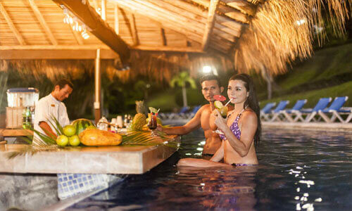 Picture of a hotel's outdoor pool bar serving drinks in Costa Rica.  The picture shows two guests under a grass hut having drinks.
