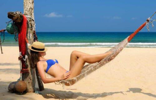 Picture of a woman in a two piece blue bikini, lying in a hammock on the beach in Costa Rica, and happy with her dental work at Premier Holistic Dental in Costa Rica