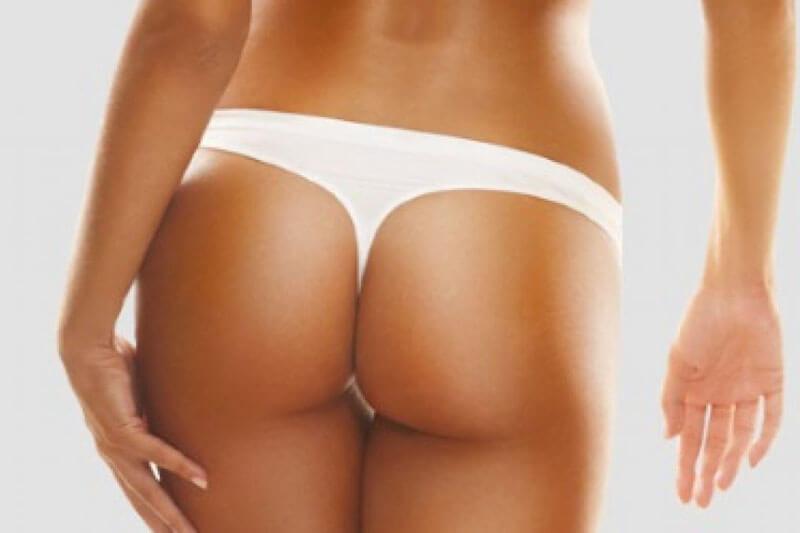 Picture of a tanned woman wearing a white thong, with her back to the camera,  happy with her Brazilian butt lift she had at Top Plastic Surgeons.