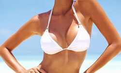Picture of a woman, happy with her breast lift with reduction and implants procedure she had at Top Plastic Surgeons in beautiful San Jose, Costa Rica.  The woman is facing the camera and wearing a white bikini top.