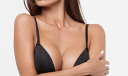 Picture of a woman, happy with her breast lift with reduction procedure she had at Top Plastic Surgeons in beautiful San Jose, Costa Rica.  The woman is facing the camera and wearing a black bikini top.