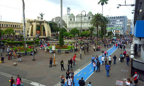 Picture of a street scene in San Jose, Costa Rica.  The picture shows a large square with many people sightseeing and visiting museums.