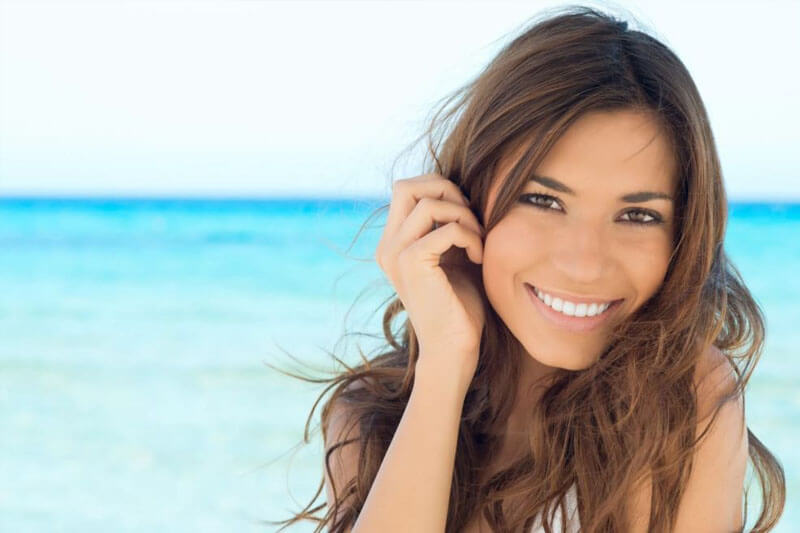Picture of a smiling woman, happy with her eyelid lift she had at Top Plastic Surgeons. The woman has long brown hair and is standing on a sandy Costa Rican beach with the ocean in the background.