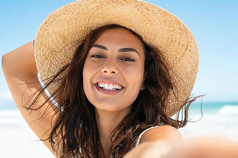 Picture of a on the beach, happy with her plastic surgery at Top Plastic Surgeons. The woman is wearing tan sun hat and sitting on a Costa Rica beach.