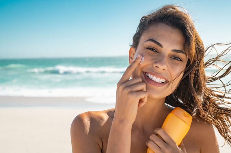 Picture of a smiling woman, happy with her nose surgery she had at Top Plastic Surgeons. The woman has long brown hair and is standing on a sandy Costa Rican beach with the ocean in the background.