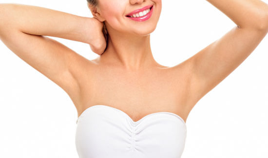 Picture of a woman holding her arms up and happy with her perfect arms liposuction procedure she had at Top Plastic Surgeons in beautiful San Jose, Costa Rica.  The woman is wearing a white top and smiling to the camera.