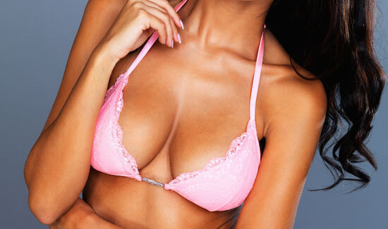 Picture of a tanned woman wearing a light pink top, and happy with her perfect breast lift with implants procedure she had at Top Plastic Surgeons in beautiful San Jose, Costa Rica.  The woman has long hair and is looking directly at the camera with her head tilted