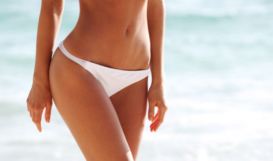 Picture of a trim woman walking along the beach and happy with her perfect lower body lift she had at Top Plastic Surgeons in beautiful San Jose, Costa Rica.  The woman is wearing a two piece white bikini and a blue ocean is in the background.