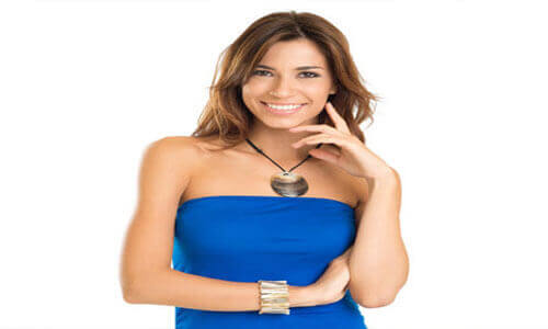 Picture of a beautiful woman  with long brown hair, wearing a blue dress, facing the camera and smiling about the plastic surgery she had at Top Plastic Surgeons in Costa Rica.