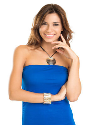 Picture of a beautiful woman wearing a blue dress and  showing her happiness with the plastic surgery procedure she had at Top Plastic Surgeons in San José, Costa Rica.