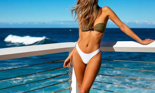 Picture of a beautiful woman, happy with her thigh lift  procedure in San Jose, Costa Rica.  The woman is wearing a two piece bikini and  is resting against a white railing while turning her head to look at the breaking waves in the ocean.