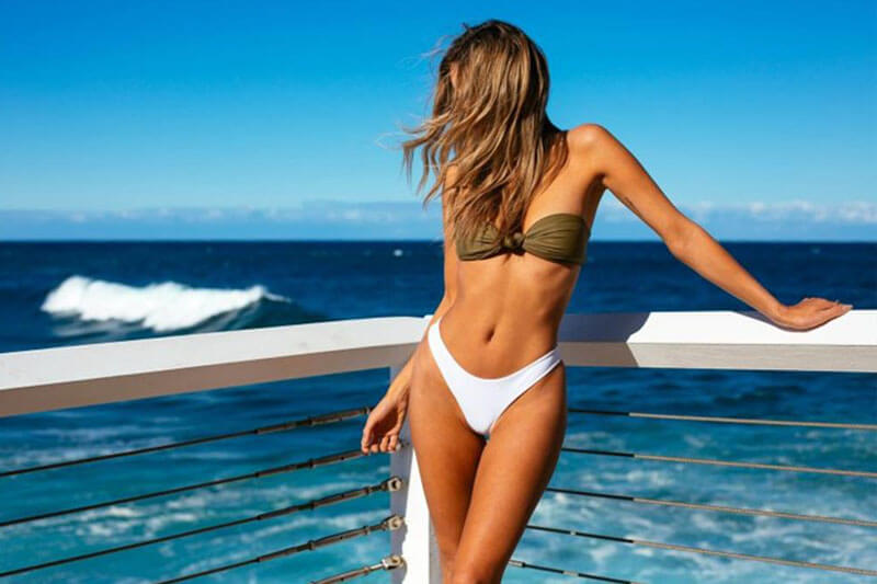 Picture of a smiling woman, happy with her thigh lift she had at Top Plastic Surgeons. The woman is wearing a white two piece bathing suit and standing against a white railing on a Costa Rica beach.