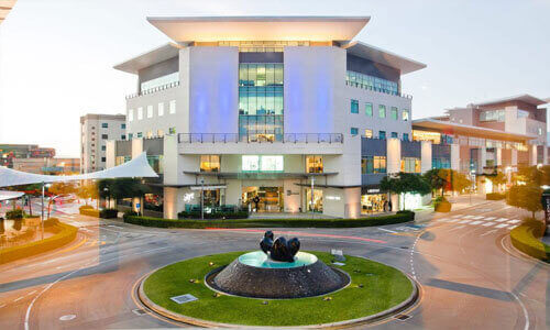 Picture of a 5 story office building in Costa Rica.  A traffic circle is shown in the picture in front of the building