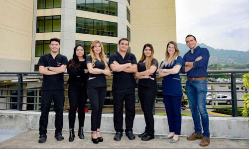 Picture of a smiling medical team at CIMA Hospital  in San José, Costa Rica.  The picture shows seven members of the medical group standing with arms folded with CIMA Hospital behind them.